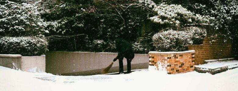 kominiarz czyści śnieg miotłą