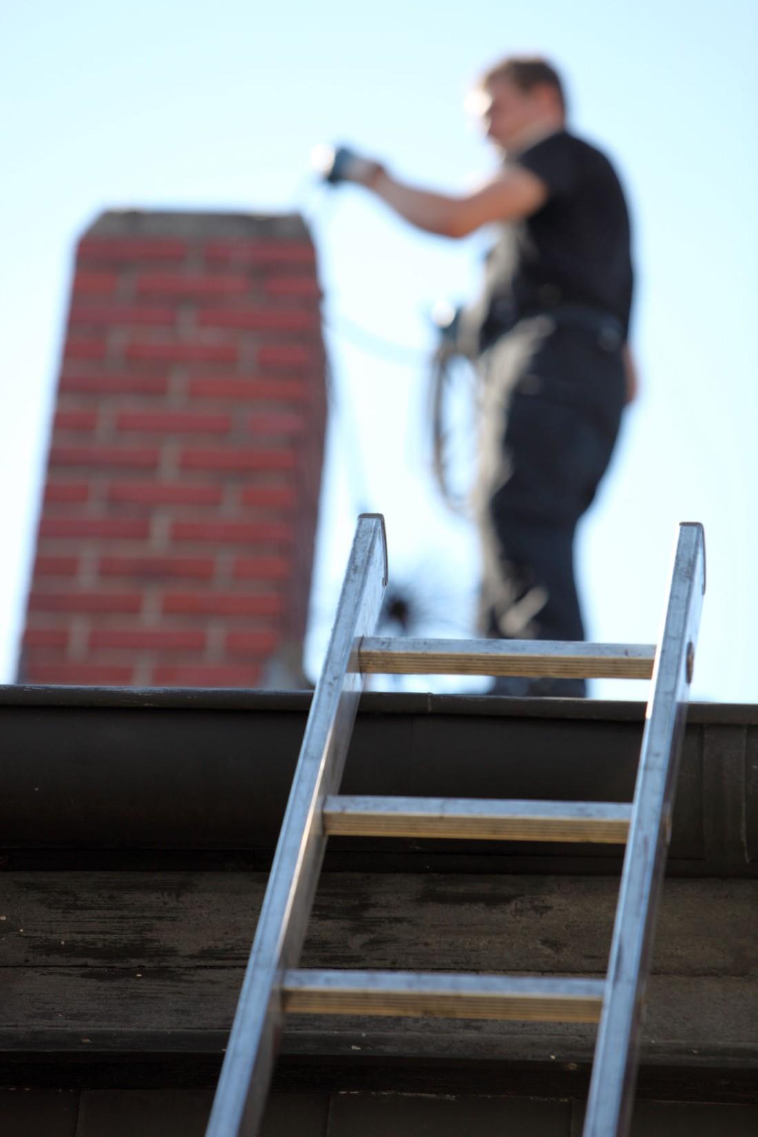 kominiarz na dachu przy kominie